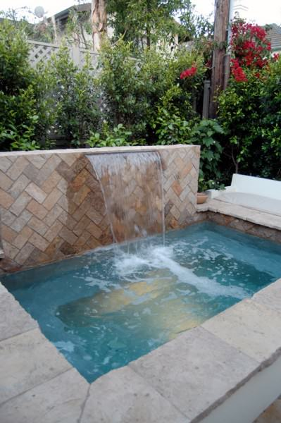 Multi level backyard with cascade waterfall, spa, built-in seating, patio, and firepit.
