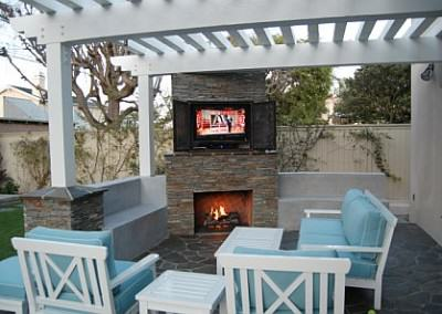 Outdoor living room with fireplace and flat screen tv