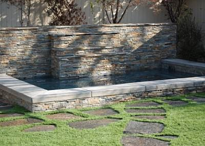 Pool / spa with waterfall and synthetic grass