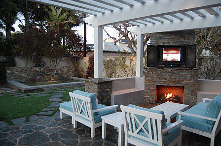 Outdoor living room with fireplace, synthetic grass, and spa