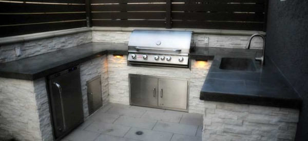 Outdoor kitchen featuring grey concrete counter tops