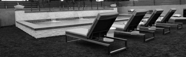 Black and white shot of classic lounge chairs and inground pool with cascades