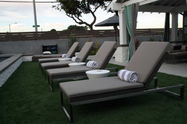 Four luxurious poolside lounge chairs with rolled up towels and side tables